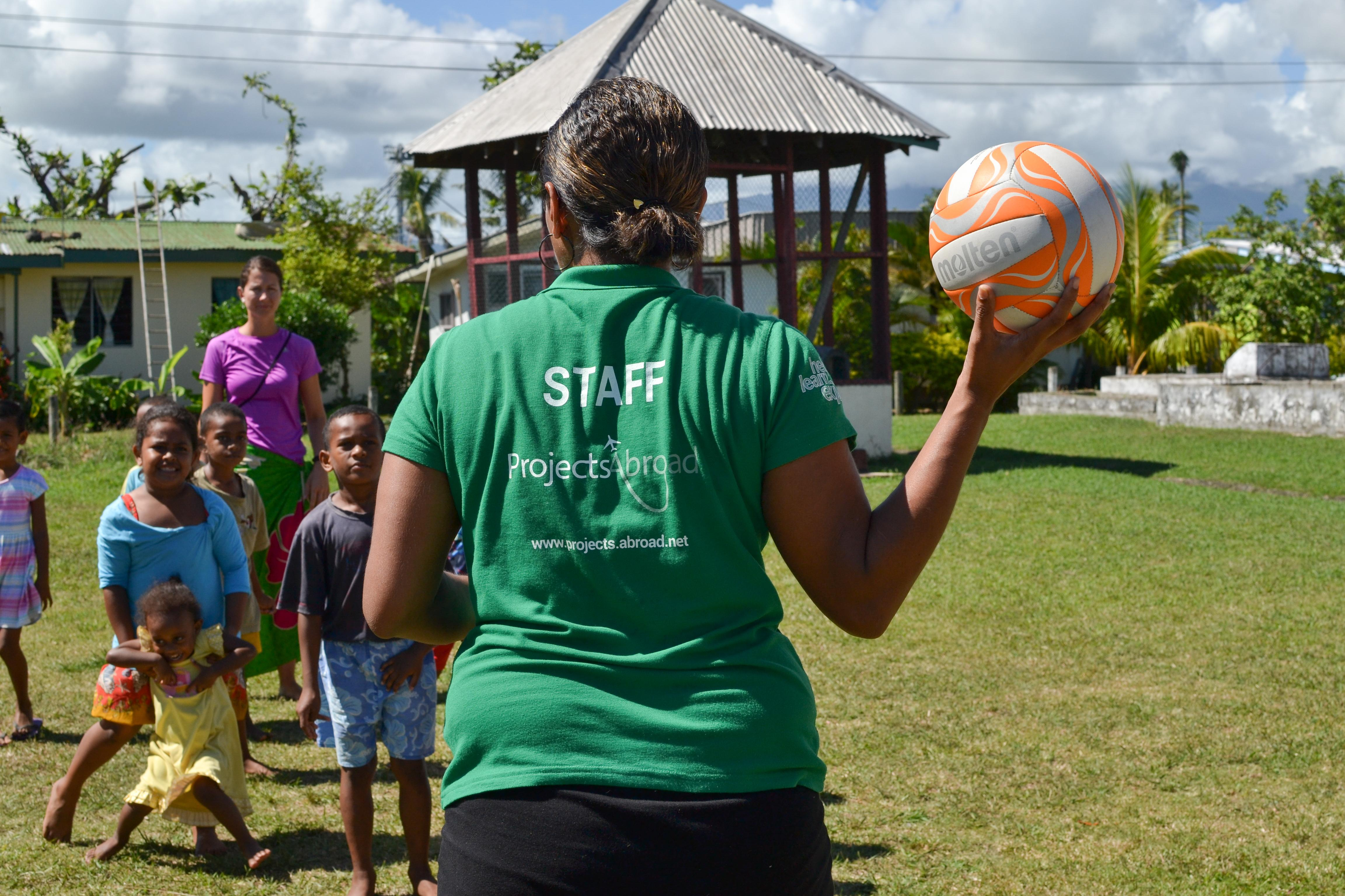 A staff member guides volunteers through a sports lesson while they are working with children abroad.